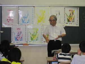 色見本を背に授業する小山さん