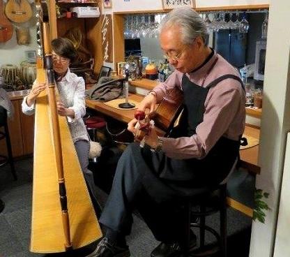 ギターとアルパで合奏する斧ご夫妻